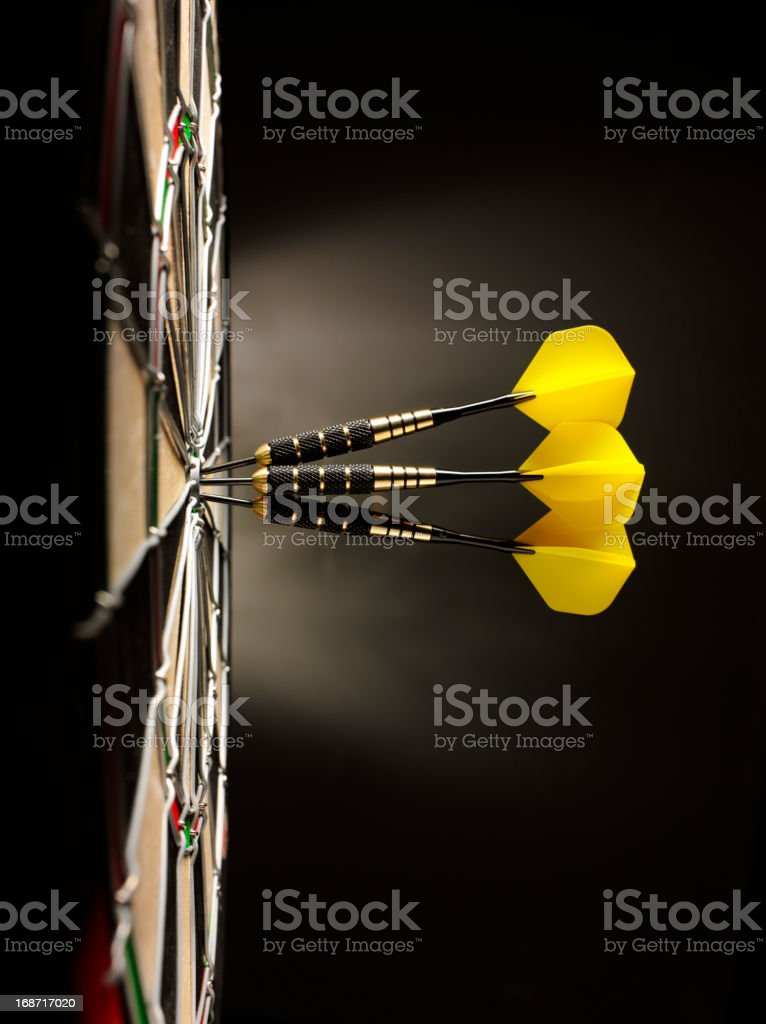 Three Yellow Darts in a Dartboard stock photo