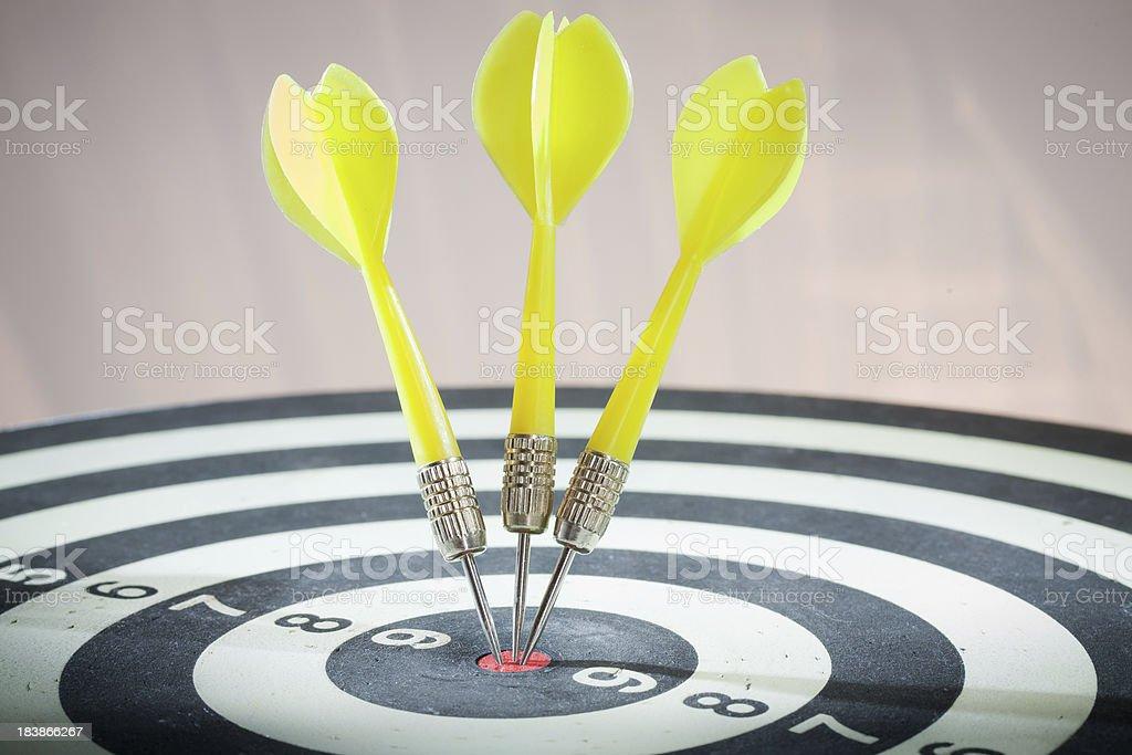 Three yellow darts in dartboard bulls eye royalty-free stock photo