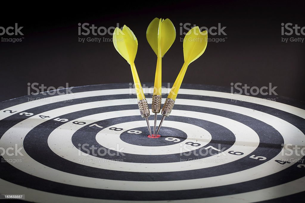 Three yellow darts in red dartboard bulls eye royalty-free stock photo