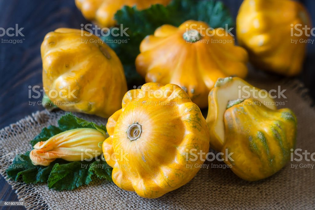 three yellow pattypan squash with leaf and flower on a stock photo