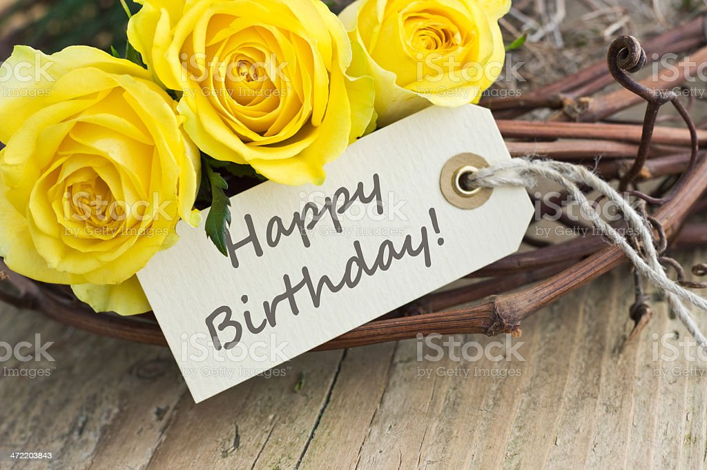 Three yellow roses with handwritten Happy Birthday tag stock photo