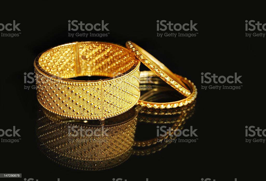 Three Yellow studded bangles on a black background royalty-free stock photo