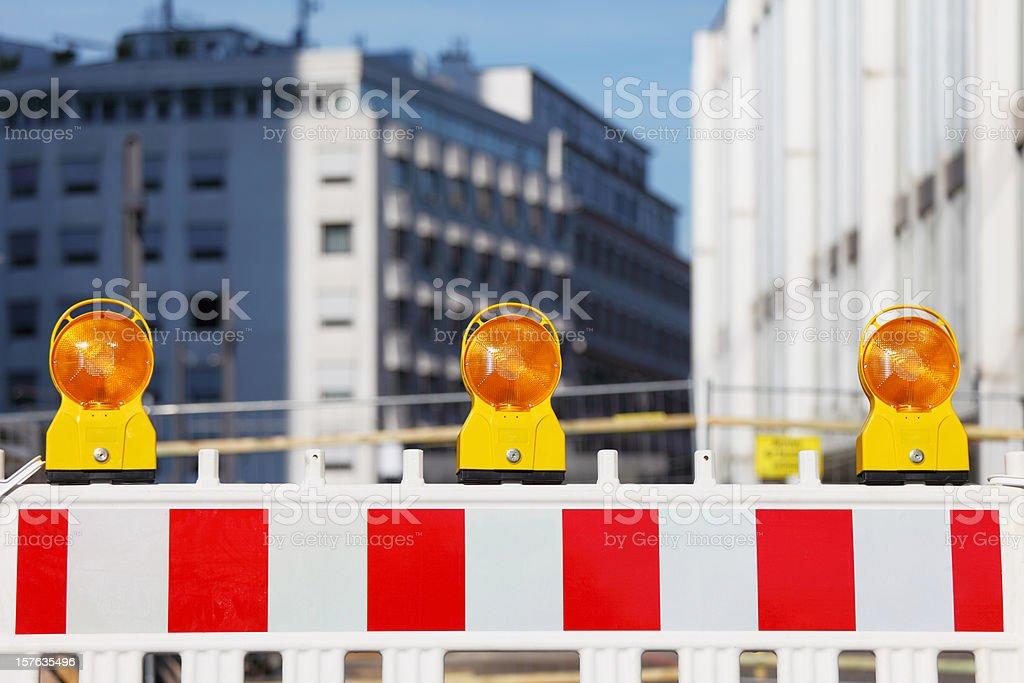 three yellow traffic warning lamps on barricade stock photo