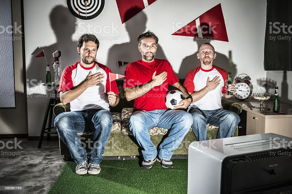 Three young adult men friends watching football: National anthem pride stock photo