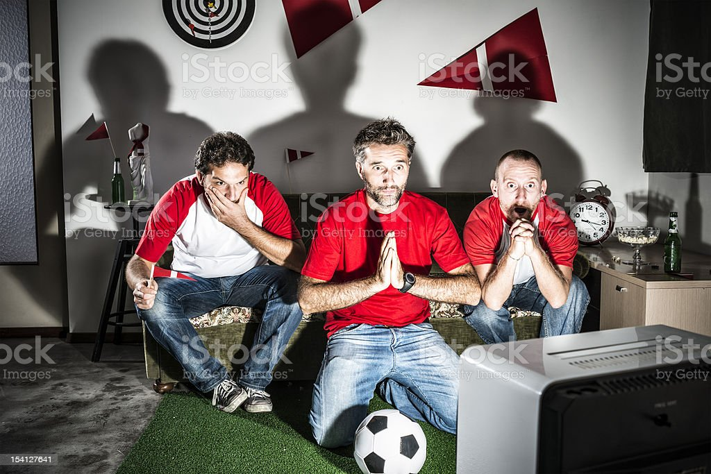 Three young adult men friends watching football: Penalty hope stock photo