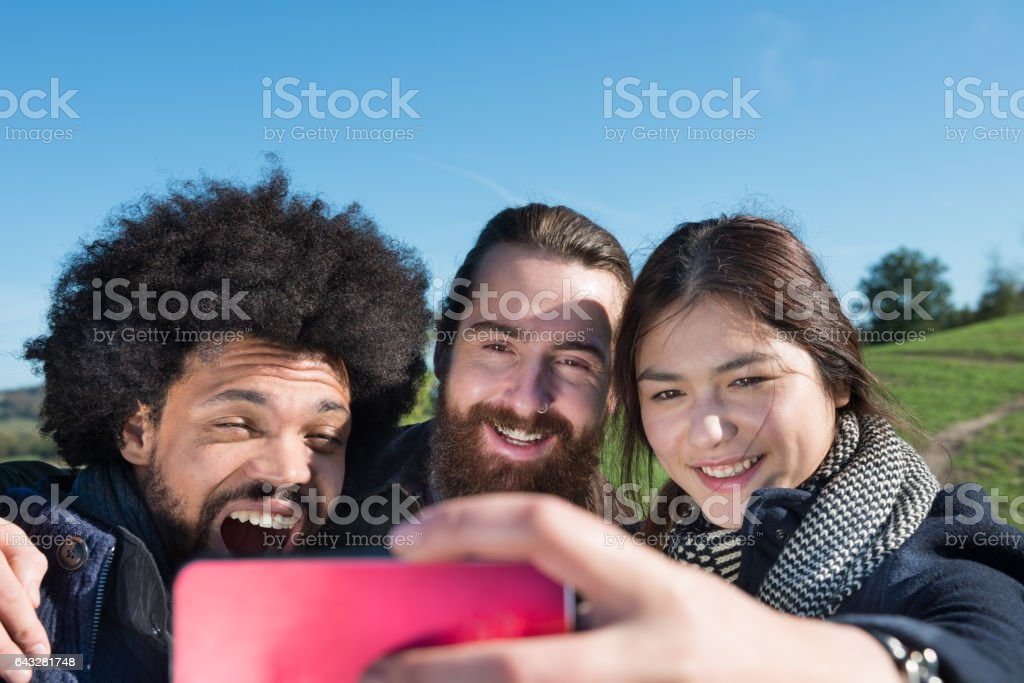 Three young adults and one mobile phone, fall clothes stock photo