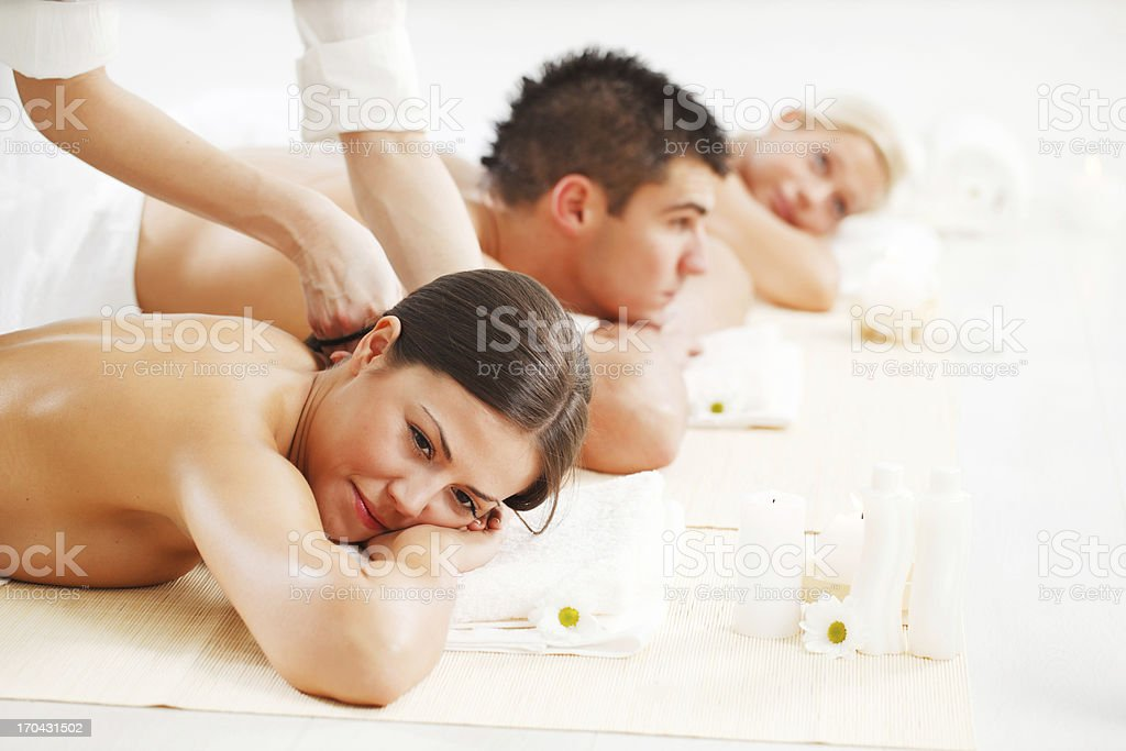 Three young adults are enjoying while having a back massage. royalty-free stock photo