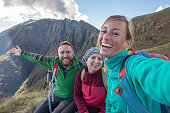 Three young adults hiking take selfie on mountain top