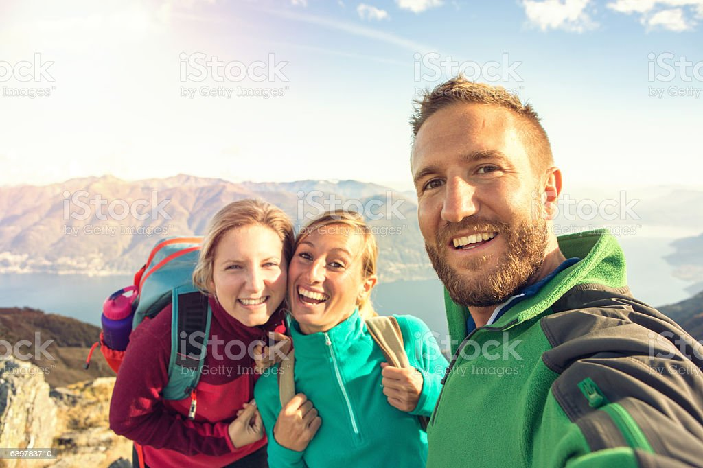 Three young adults hiking take selfie on mountain top stock photo