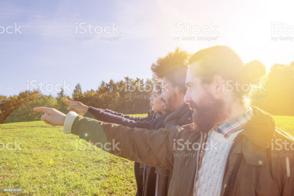 Three young adults pointing forward stock photo