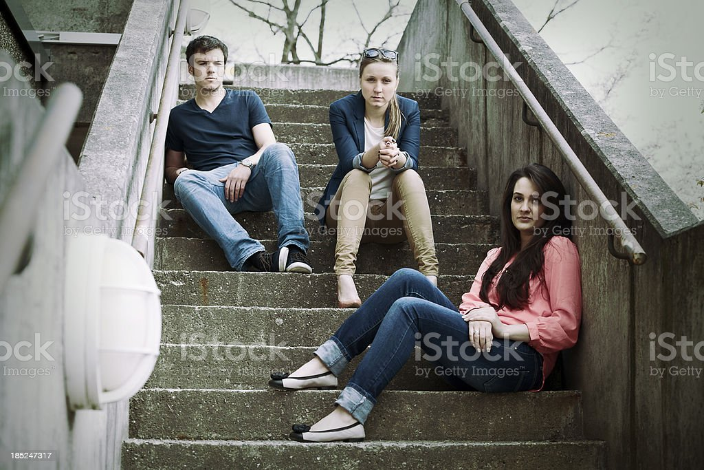 Three young adults sitting on stairs stock photo