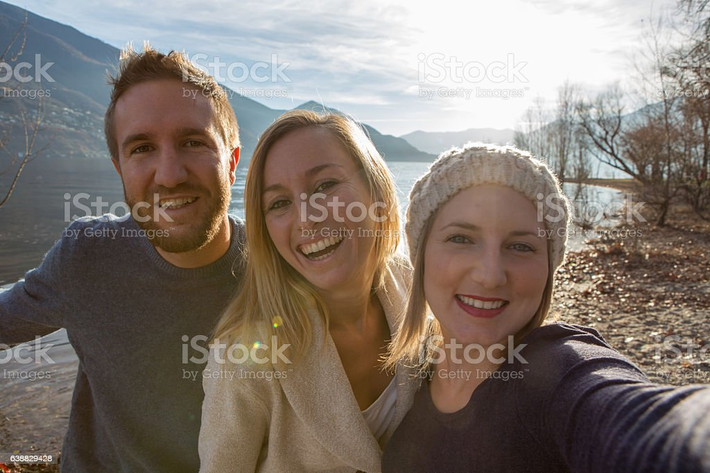 Three young adults taking selfie by the lake at sunset stock photo