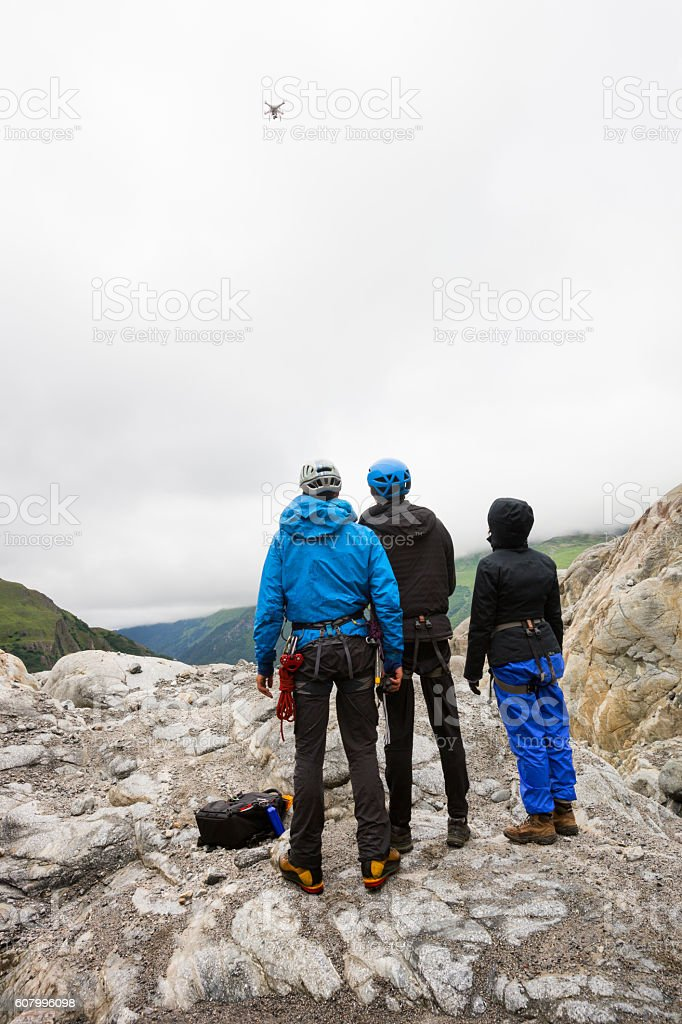 Three young adults watching a drone stock photo