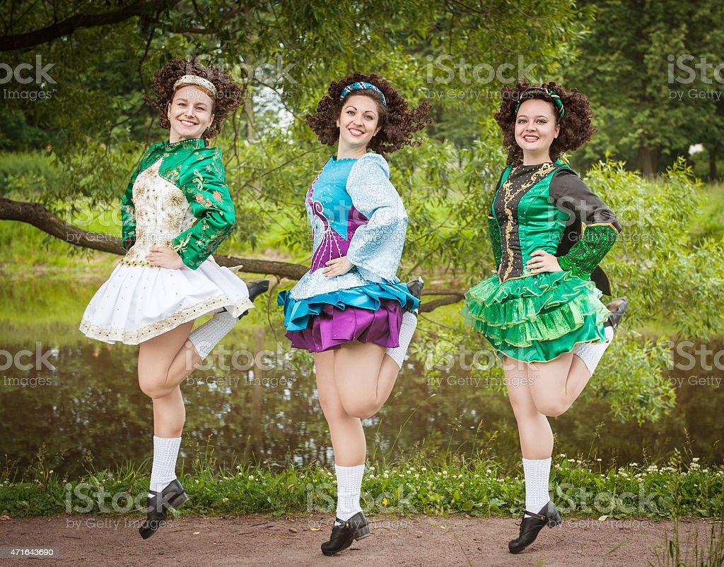 Three young beautiful girls in irish dance dress dancing stock photo