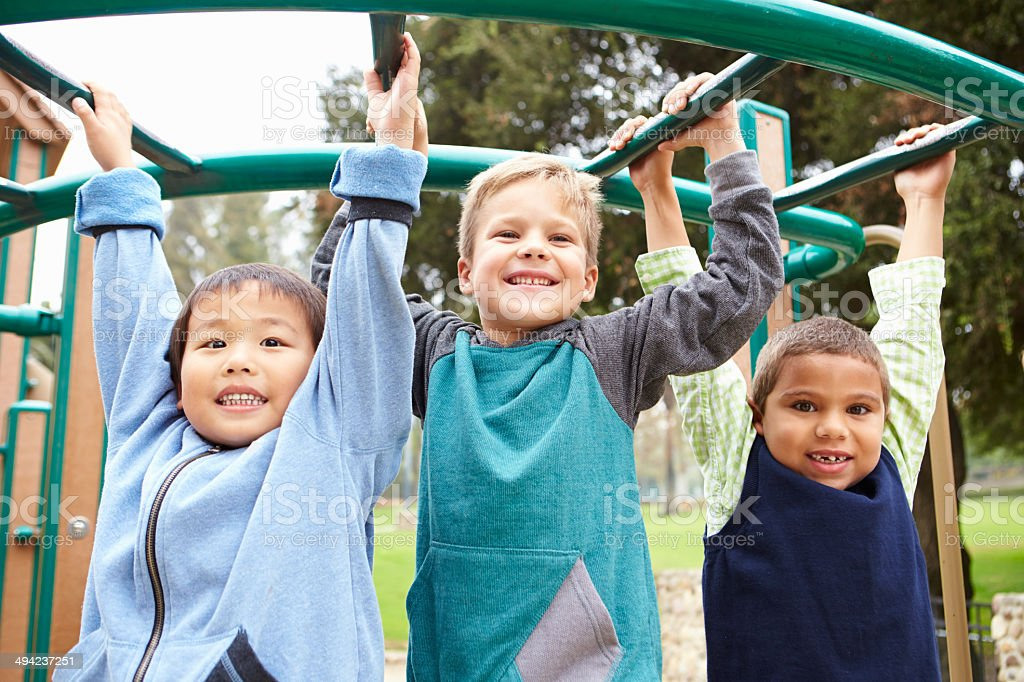 Three Young Boys On Climbing Frame In Playground stock photo