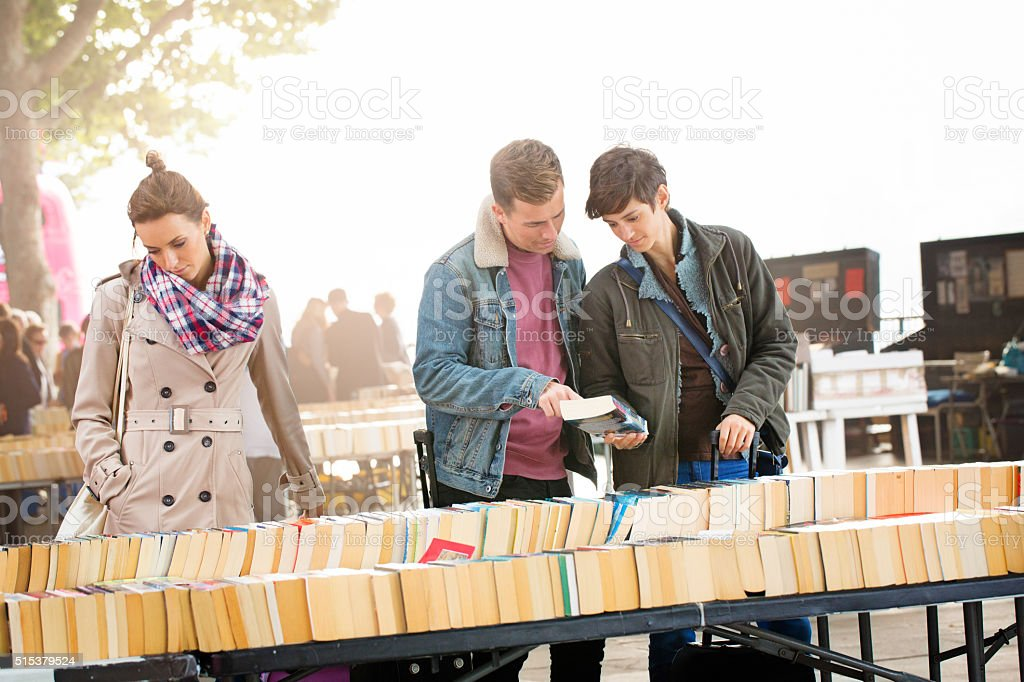 Three young British people shopping for books outdoors stock photo