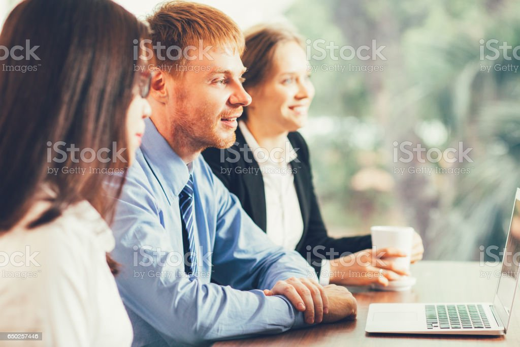 Three Young Business People Having Meeting stock photo