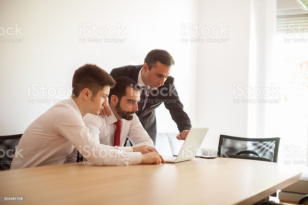 Three young businessman working in office stock photo
