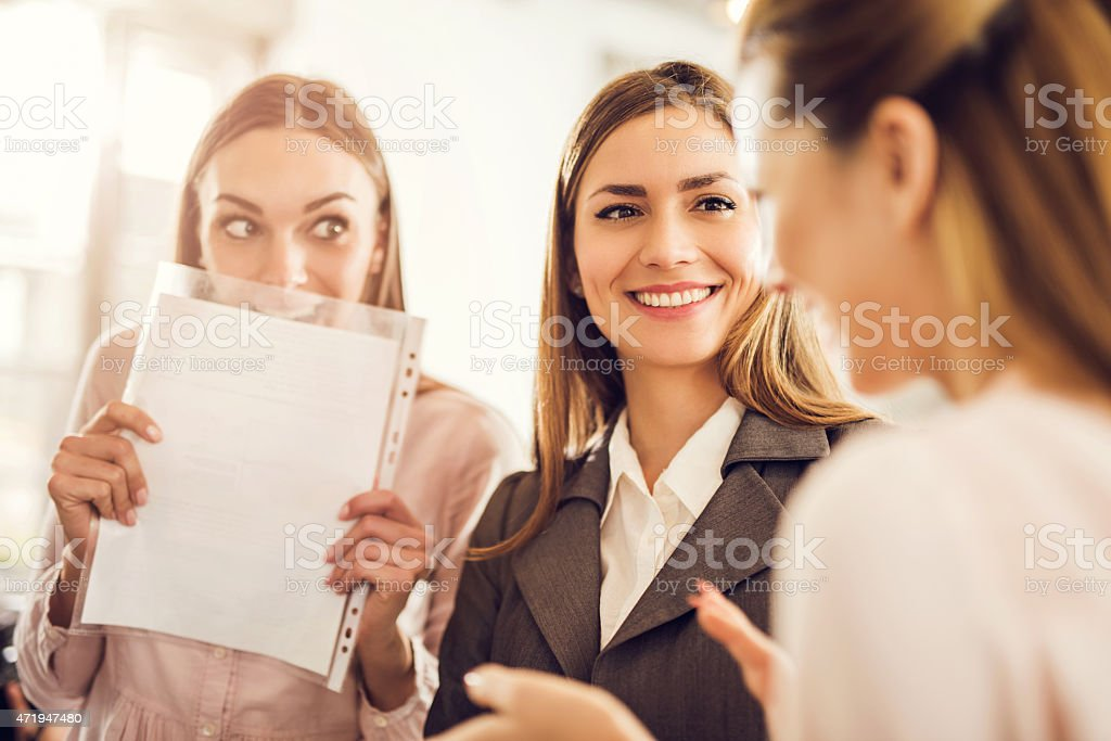Three young businesswomen gossiping about someone. stock photo