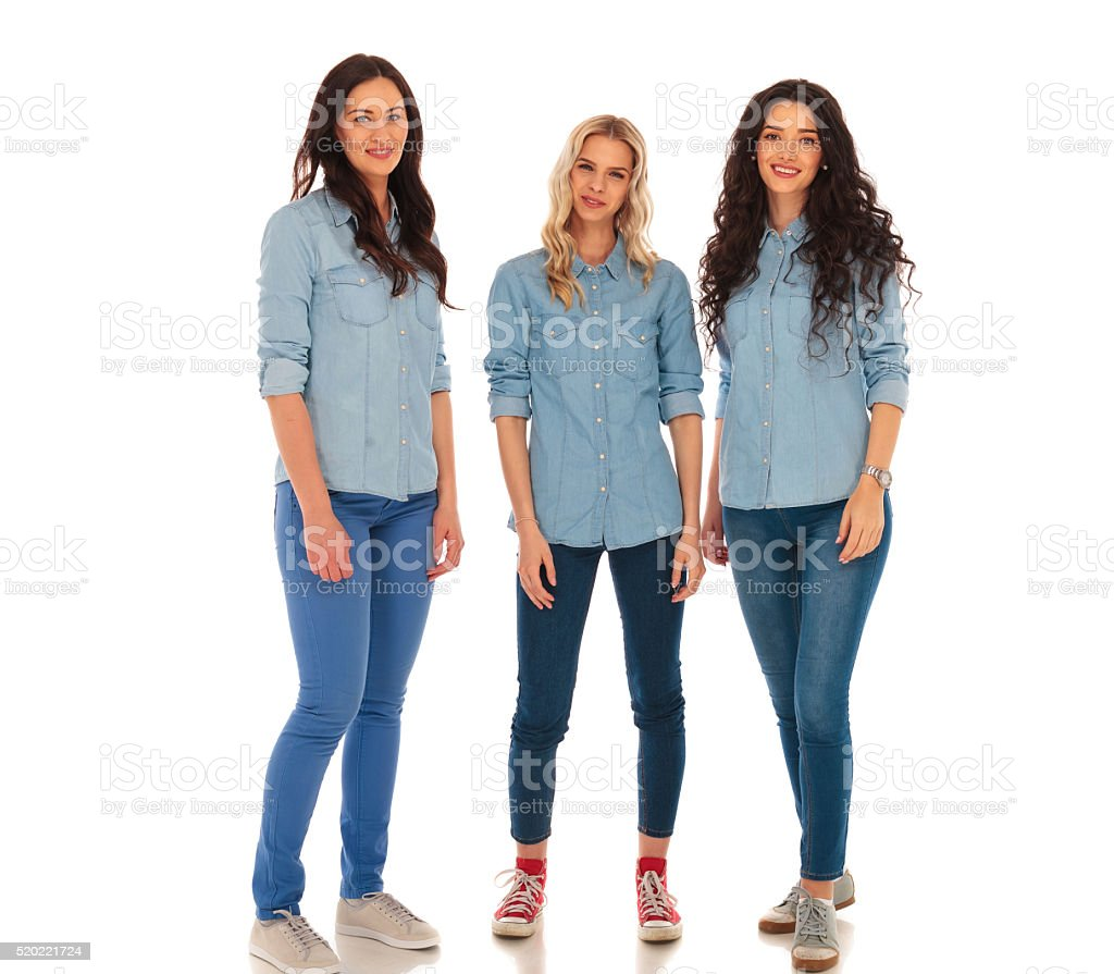 three young casual women in jeans clothes standing together stock photo
