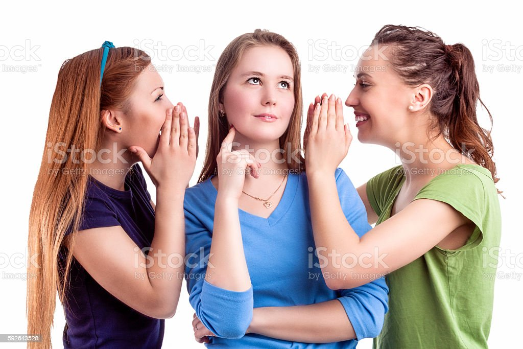Three Young caucasian Girlfriends Sharing Their Secrets Whispering to Ears. stock photo