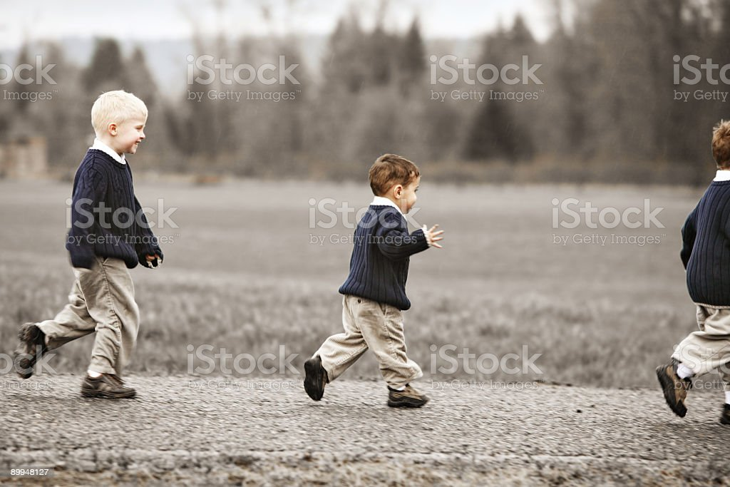 Three Young Children Running Down a Road stock photo