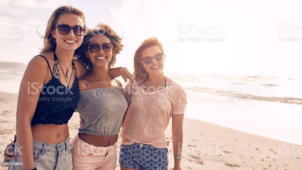 Three young female friends on the sea shore stock photo