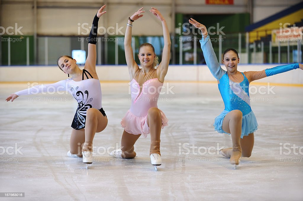 Three young female skaters posing on ice royalty-free stock photo