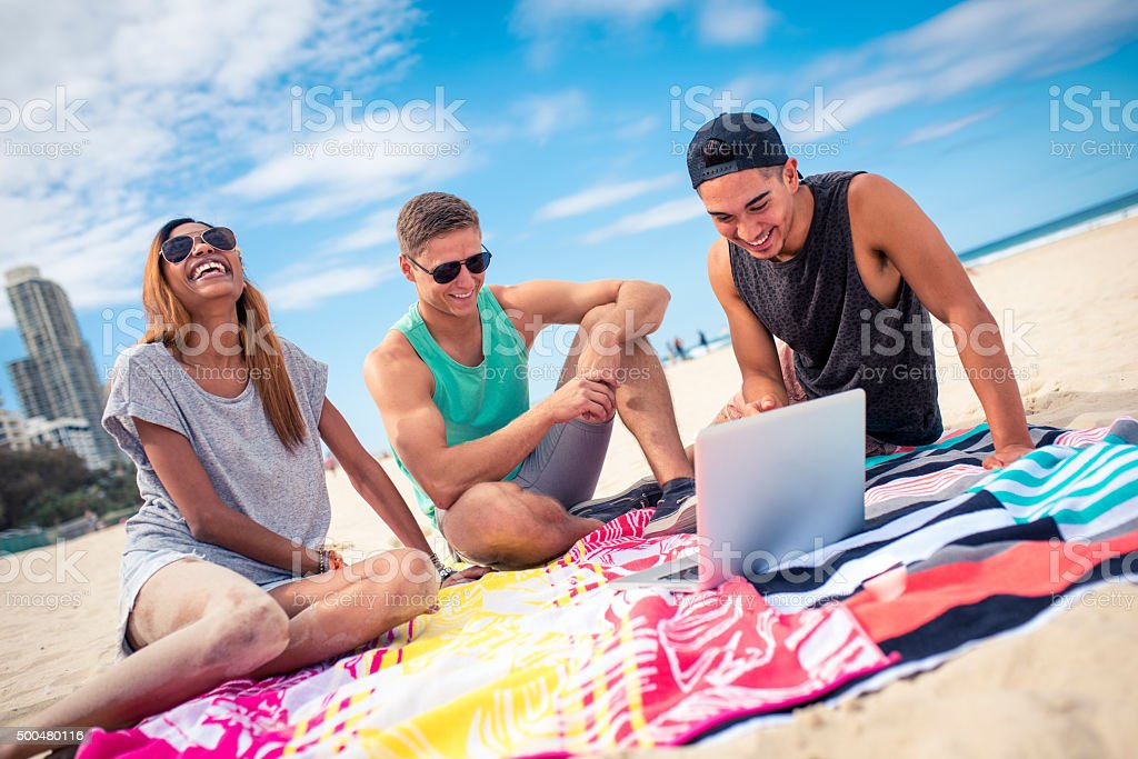 Three young friends having fun on the beach stock photo