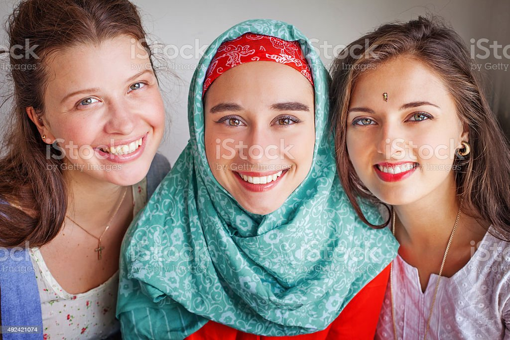Three young girls standing happily together in the corner