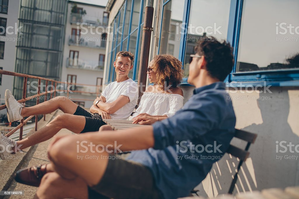 Three young friends relaxing at outdoor cafe stock photo