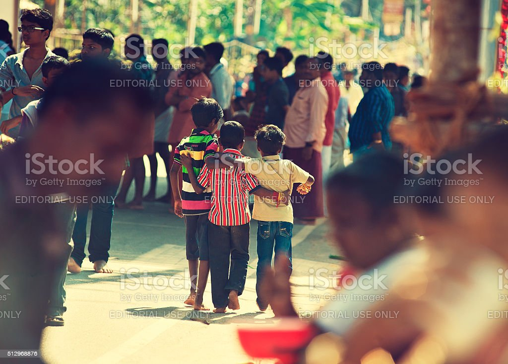 Three young friends walking through crowd. stock photo