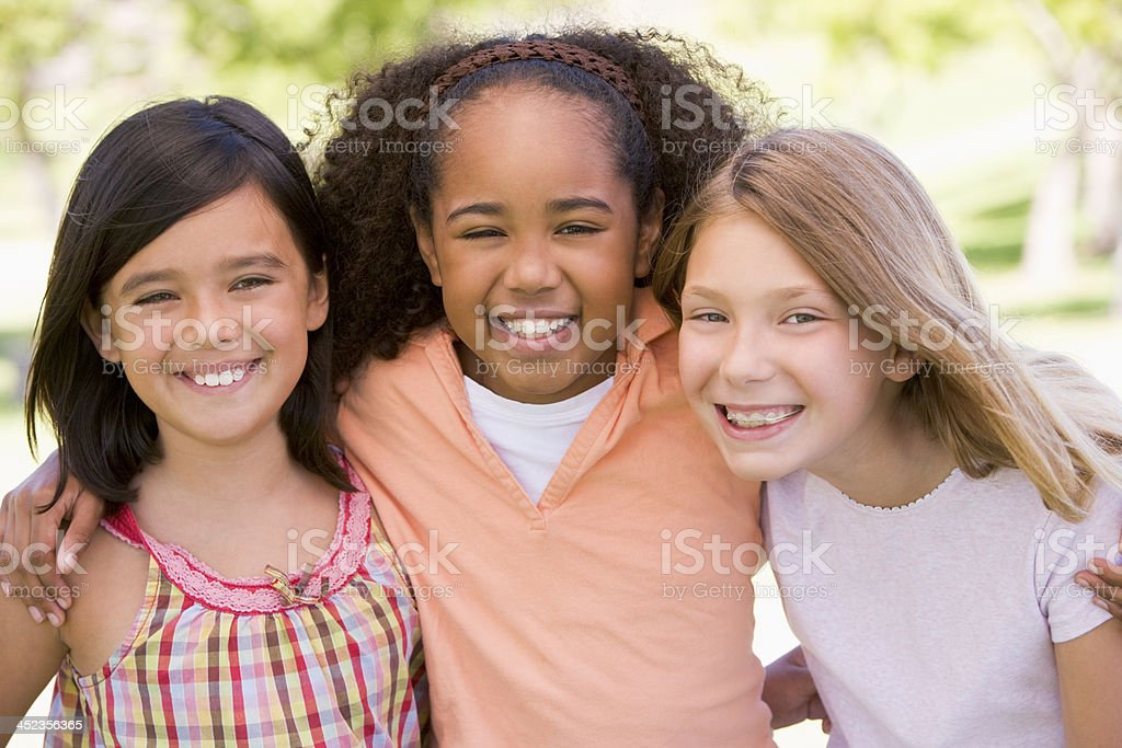Three young girl friends outdoors smiling royalty-free stock photo