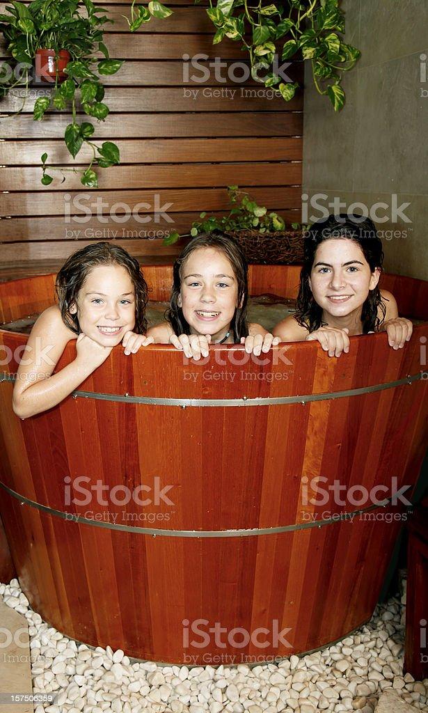 Three young girls i a furo bathtub stock photo