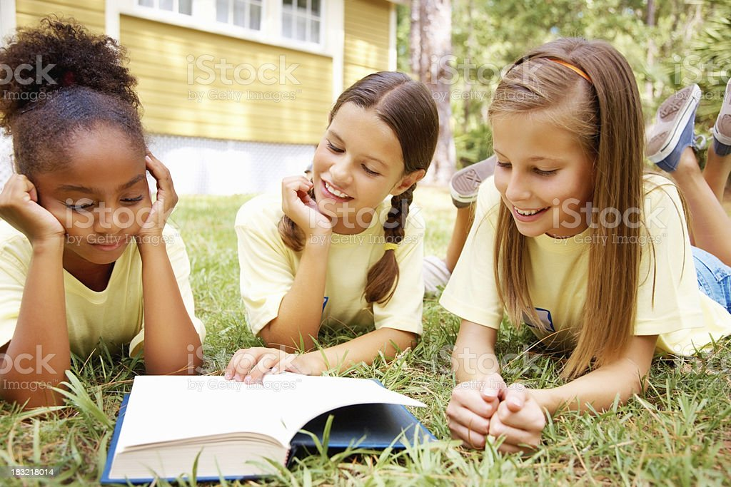 Three young girls lying in grass while reading book royalty-free stock photo