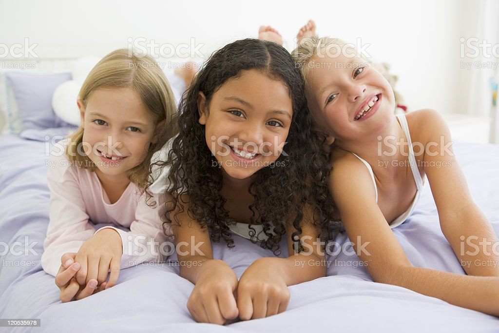 Three Young Girls Lying On Bed In Their Pajamas stock photo