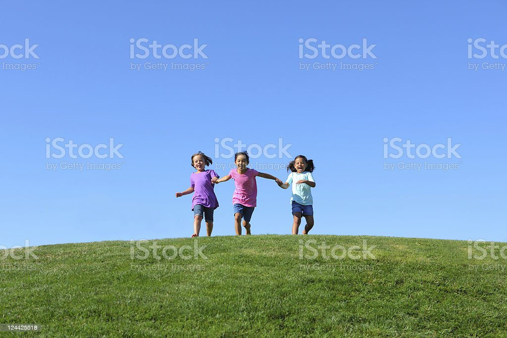 Three young girls running together holding hands royalty-free stock photo
