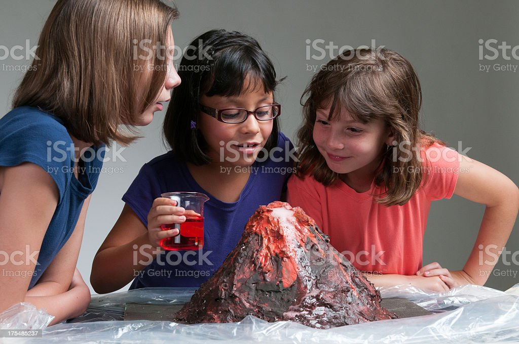 Three young girls studying volcanoes stock photo
