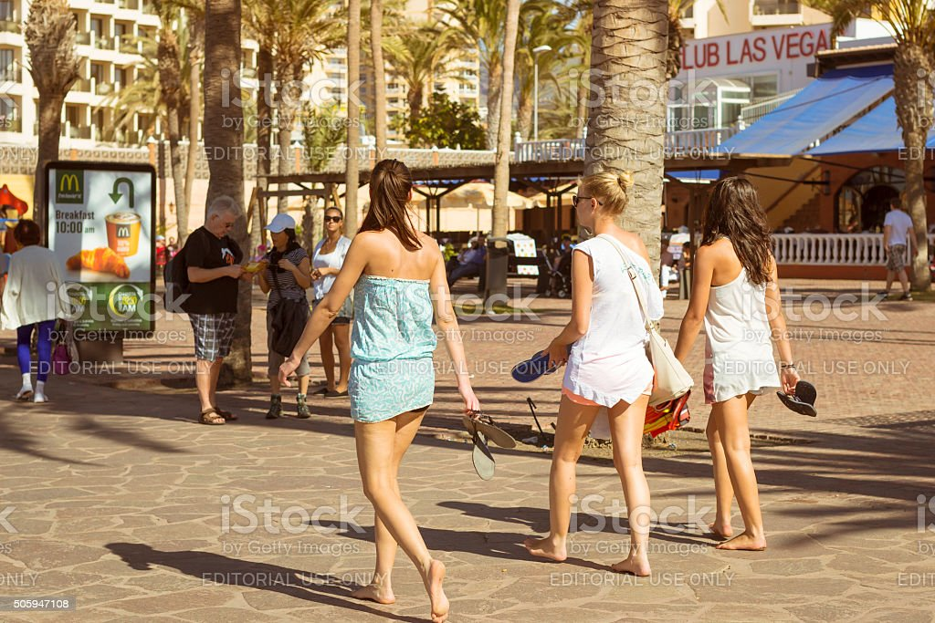Three young girls walk along the promenade stock photo