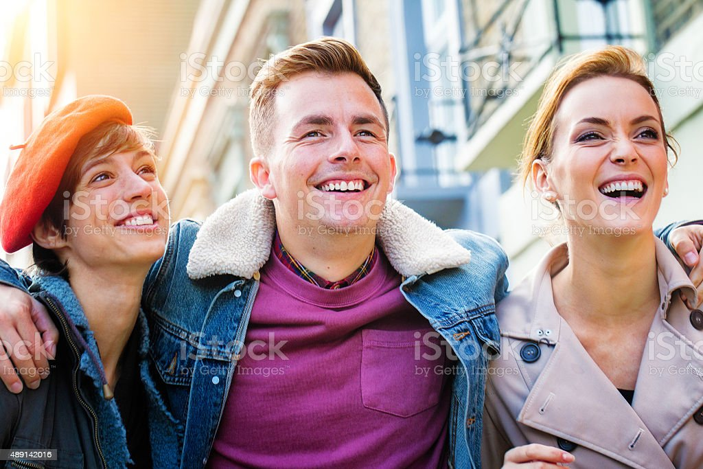 Three young happy British friends walking with big smiles stock photo