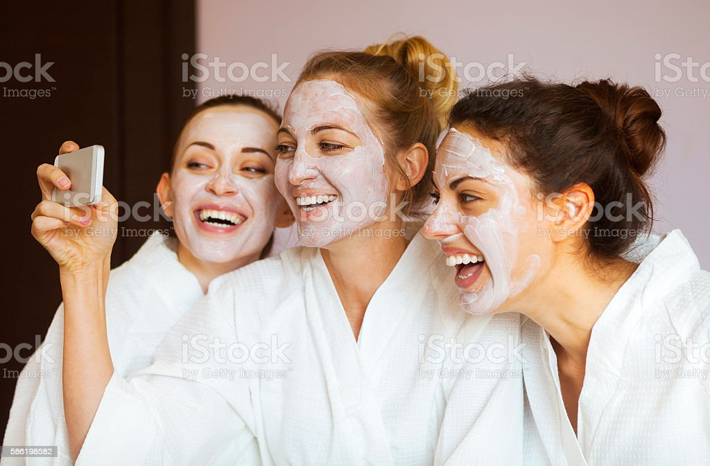 Three young happy women with face masks at spa resort. stock photo