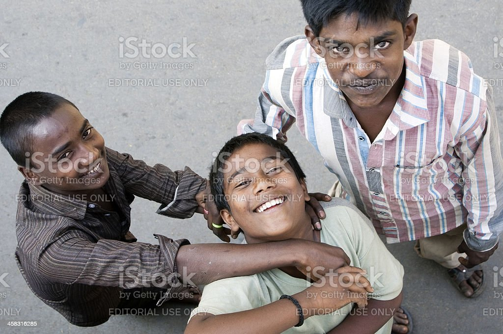 Three young Indian males smiling up at camera royalty-free stock photo