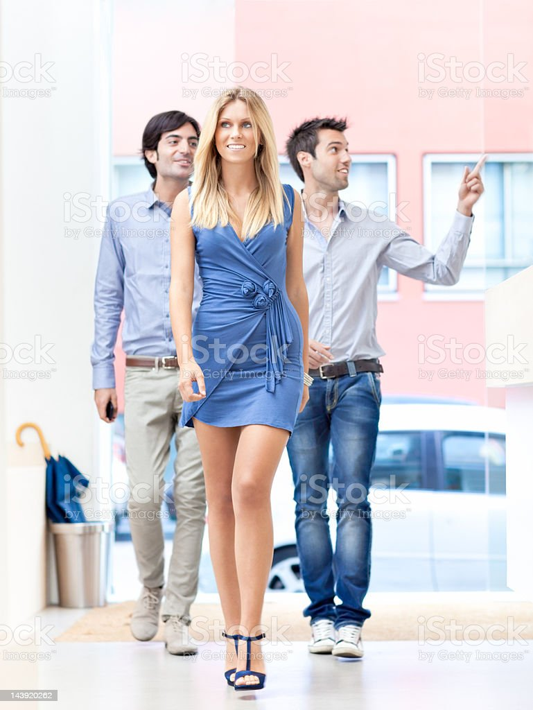 Three young Italian friends entering aperetivo bar royalty-free stock photo