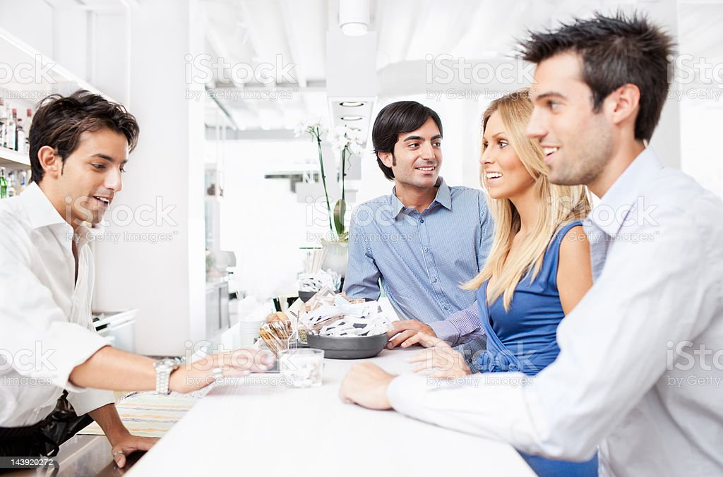 Three young Italian friends ordering drinks in aperetivo bar royalty-free stock photo