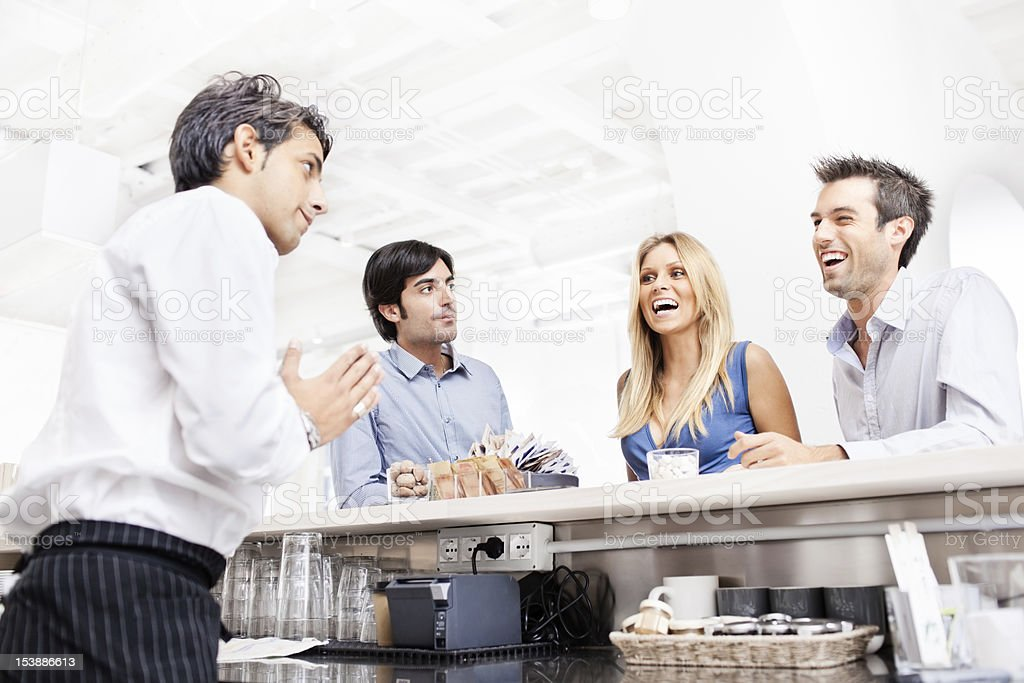 Three young Italian friends ordering drinks in aperetivo bar stock photo