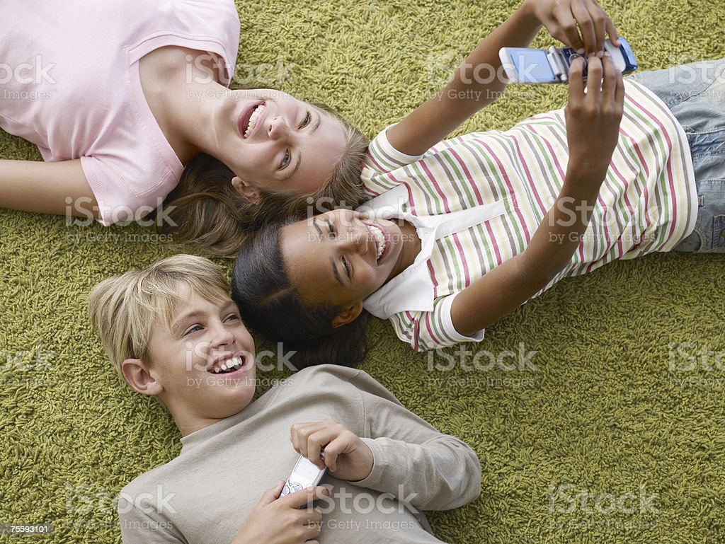 Three young kids two with cellular phones royalty-free stock photo
