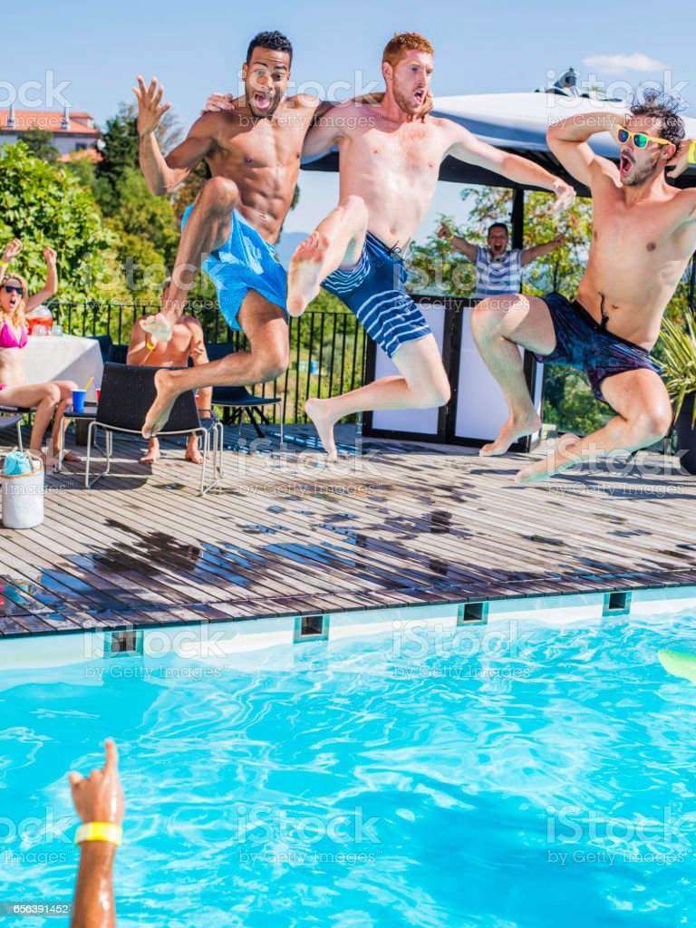 Three young men in swimming shorts jumping into pool stock photo