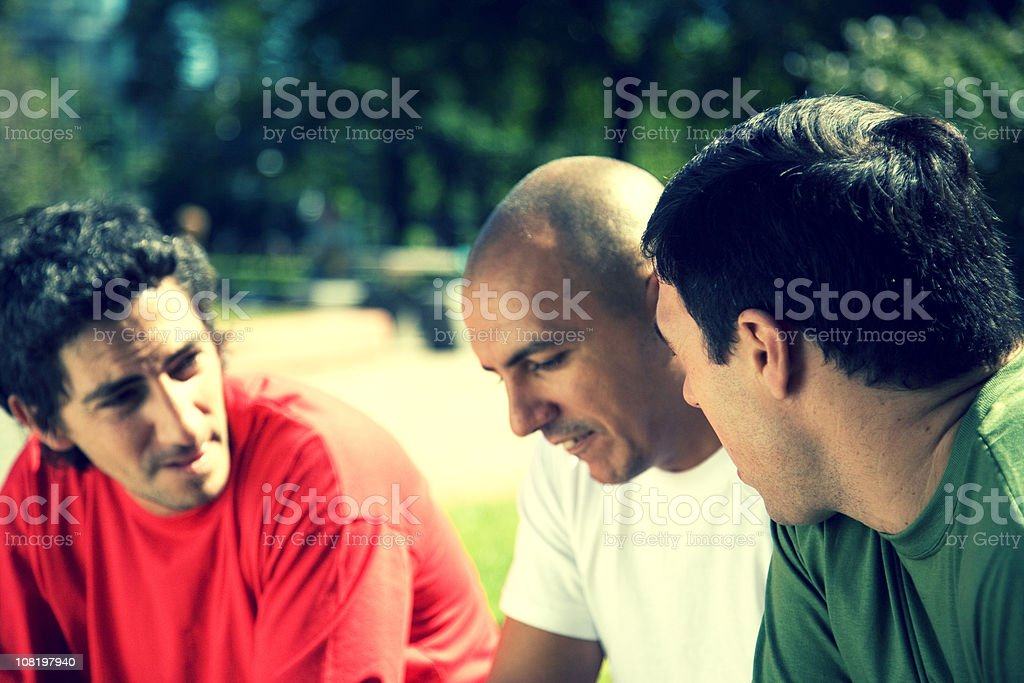 Three Young Men Talking Outside in Park royalty-free stock photo