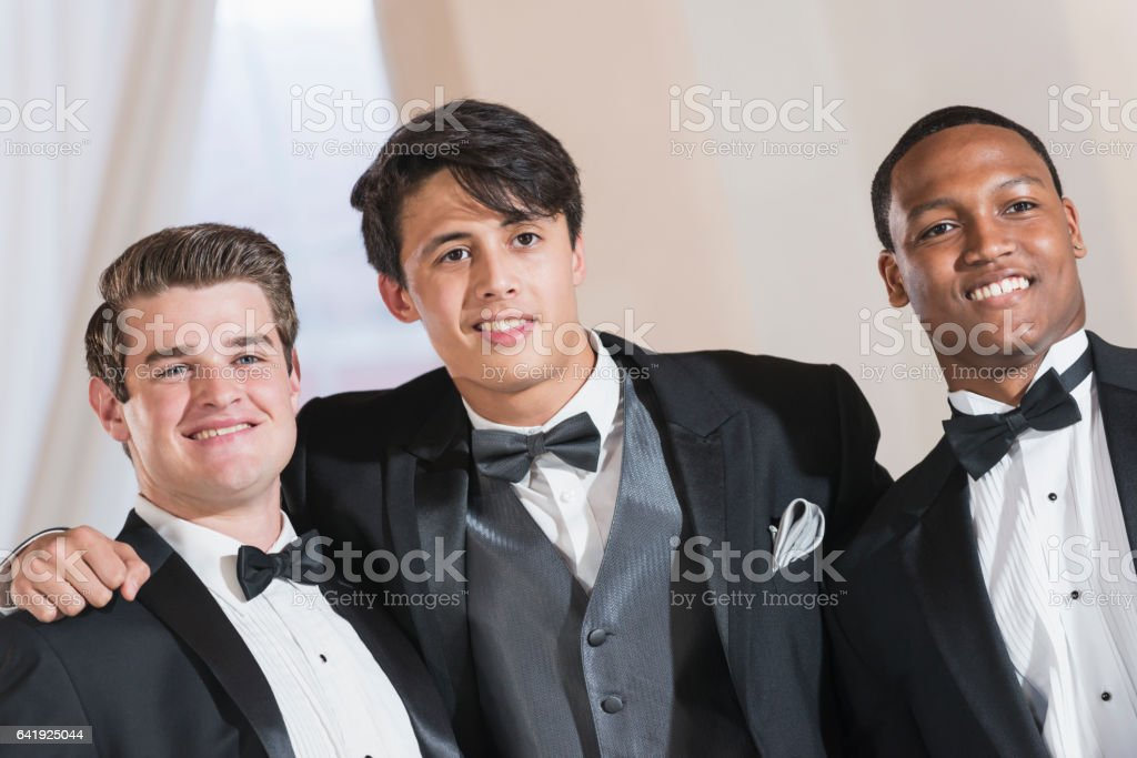 Three young men wearing tuxedos stock photo