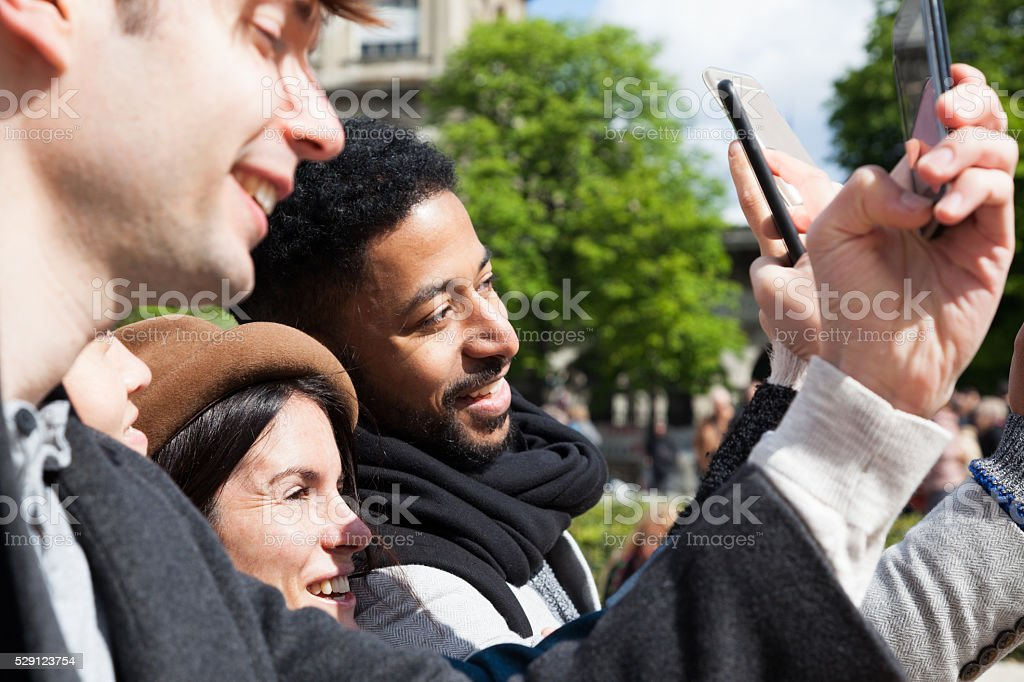 three young multiracial friends takes selfies in Paris sun stock photo